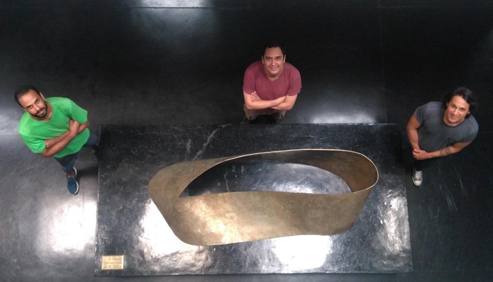 Três pessoas e uma escultura da faixa de Moebius